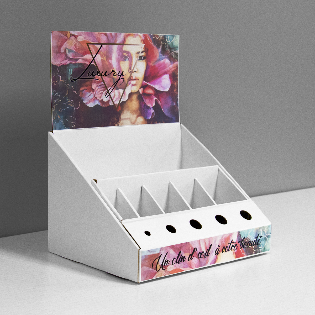 Cardboard counter display with inserts and slots for makeup products and a header - printed